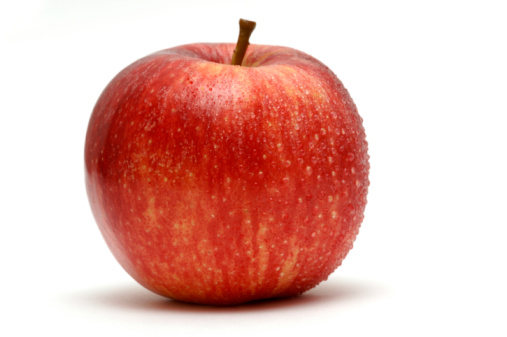 apple covered in water droplets against white