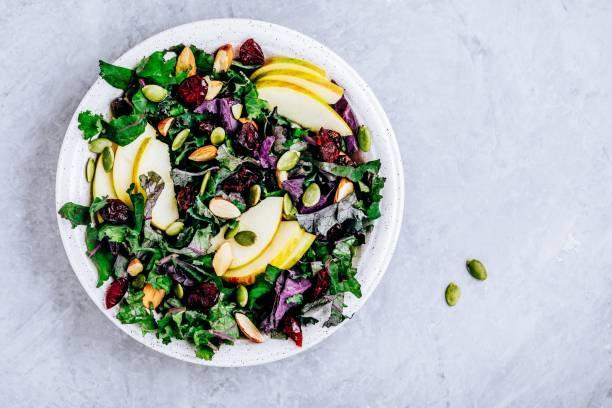 appel cranberry kale salade kom met droge veenbessen, amandelen en pompoenpitten. - salade stockfoto's en -beelden