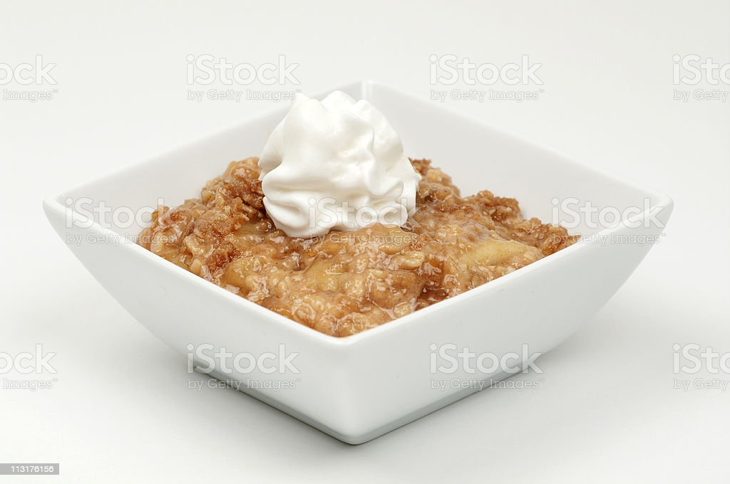 Apple crisp topped with whipped cream in a white bowl stock photo