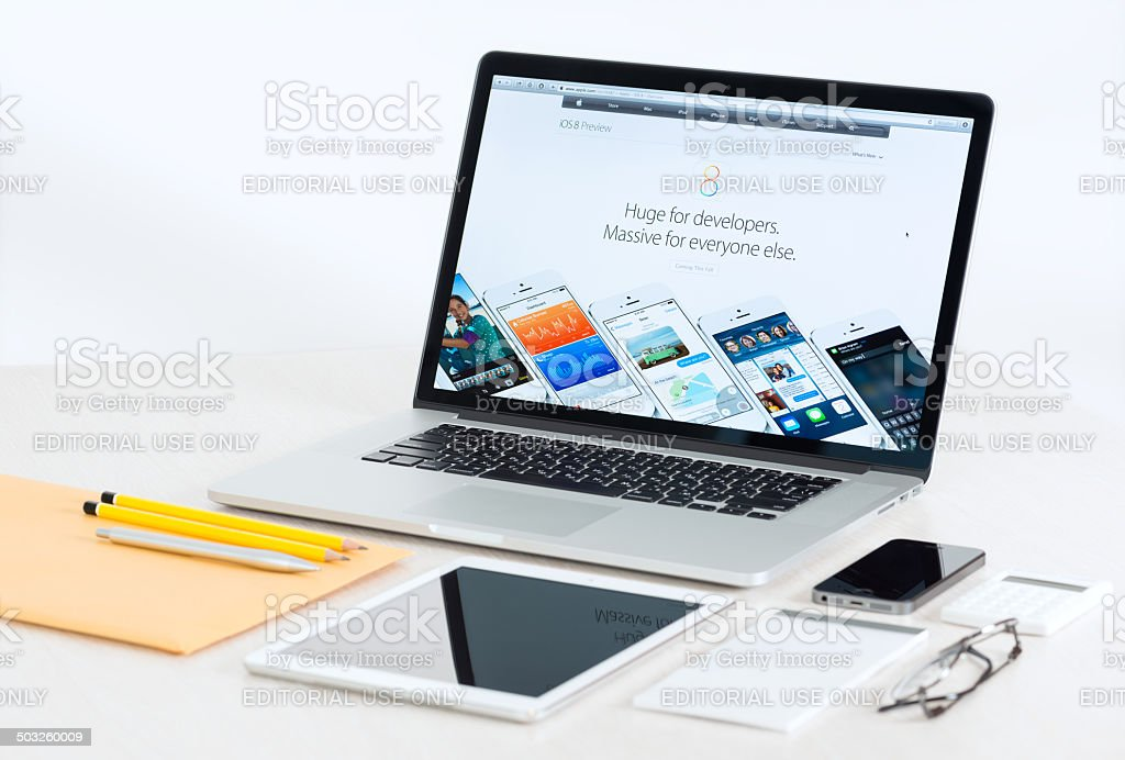 Dispositivos Apple em uma mesa a apresentar iOS 8 - foto de acervo