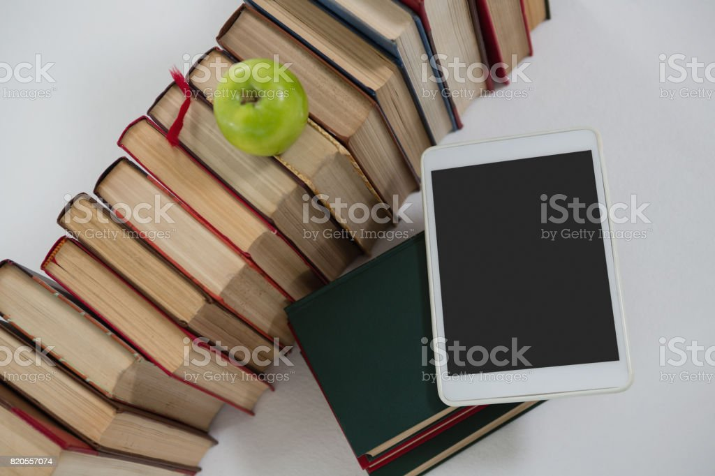 Apple, digital tablet and books on white background stock photo