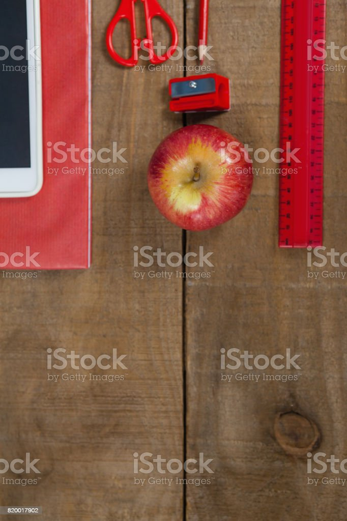 Apple, digital tablet and school supplies on wooden table stock photo