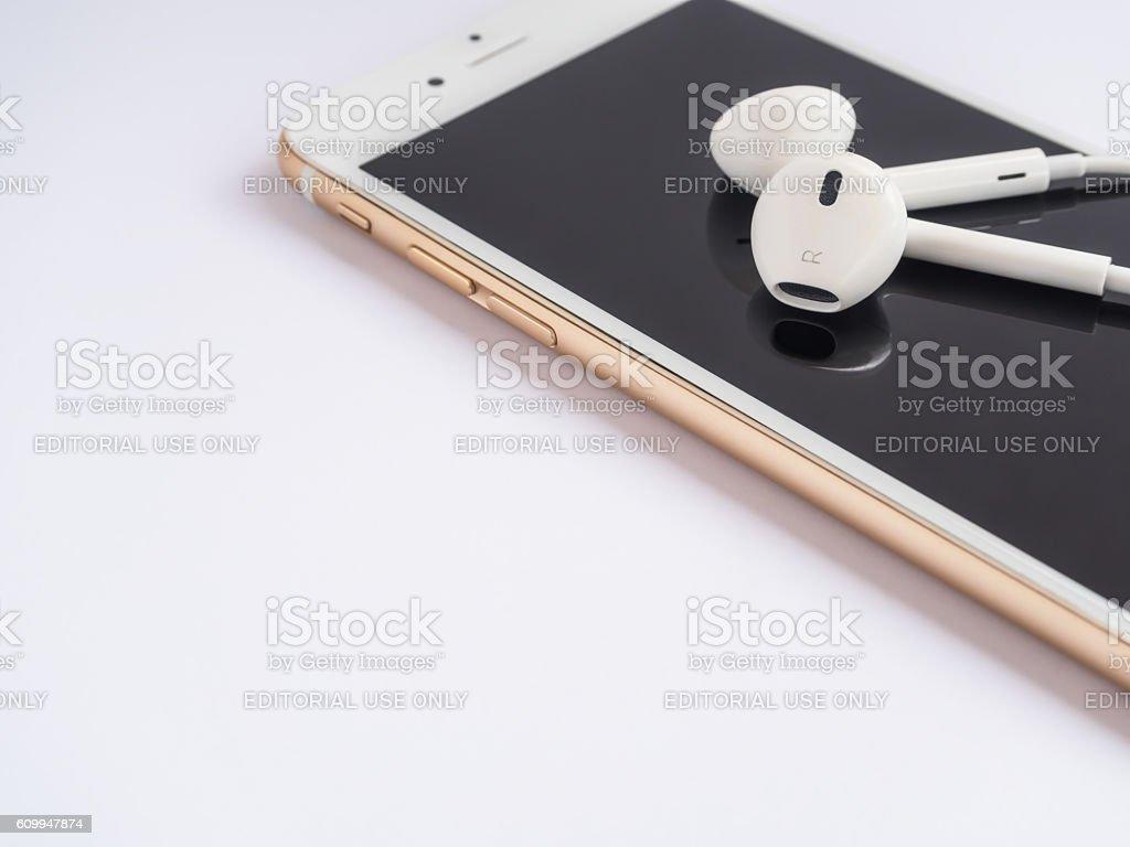 Apple EarPods on top of Apple iPhone stock photo