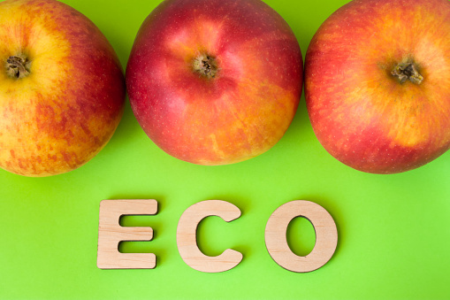 istock Apple Eco product or food. Three apples are on green background with text eco wooden letters. Example of sustainable environmentally or ecological friendly product, Eco innovation or green marketing 930489470
