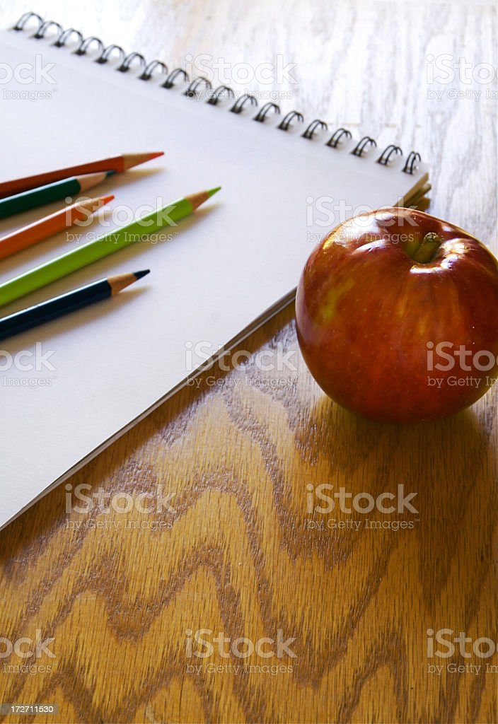 Photo of an apple on a desk with a blank notebook and colored pencils.