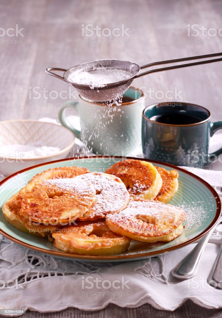 Apple fritters with icing sugar sifting over stock photo