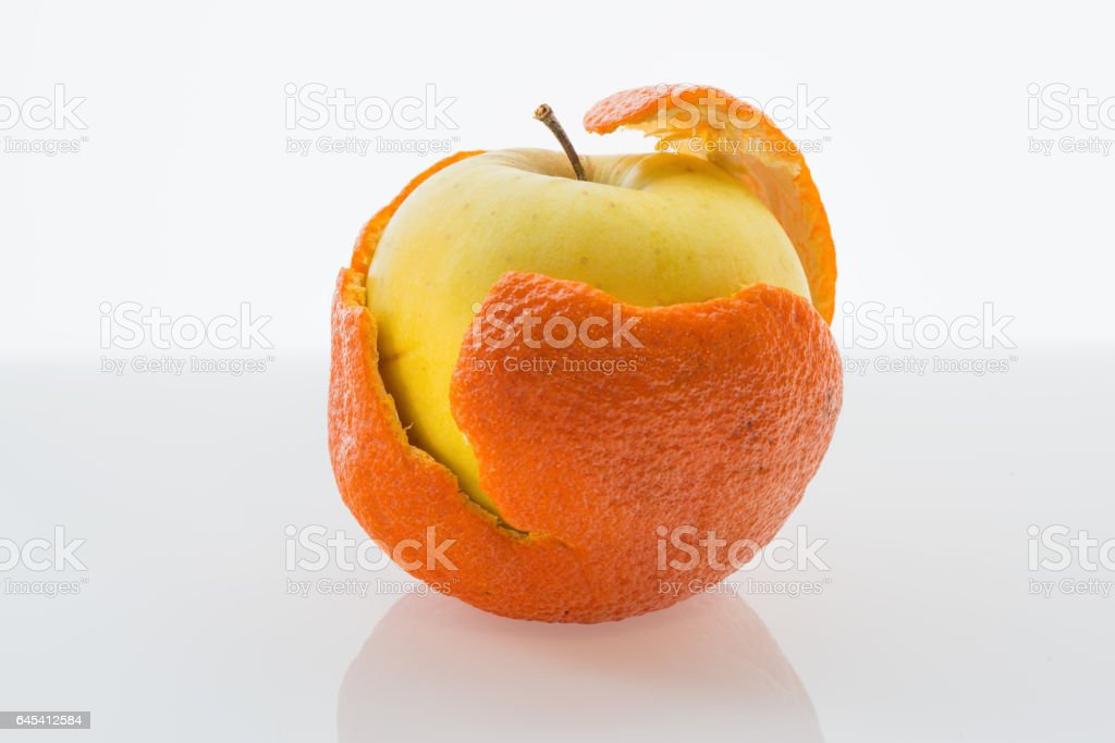 Apple in a tangerine peel стоковое фото