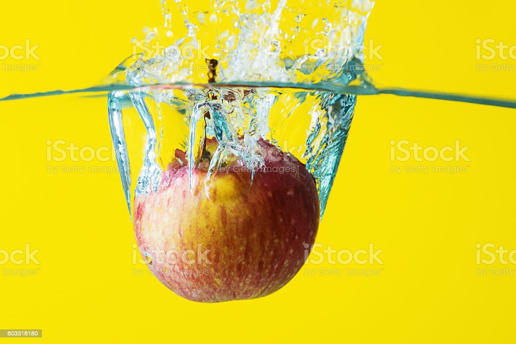 Apple in water with splash on yellow background
