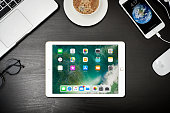 Kyiv, Ukraine - Fabruary 6, 2018: Apple iPad Gold with iPhone 8 plus and MacBook Pro on black wooden background, top view. Apple Inc. is an American multinational corporation that designs, develops, and sells consumer electronics.