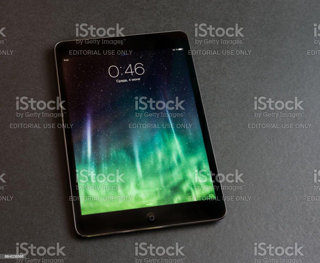Apple iPad mini displaying iOS 7 screen saver screen, russian version. stock photo