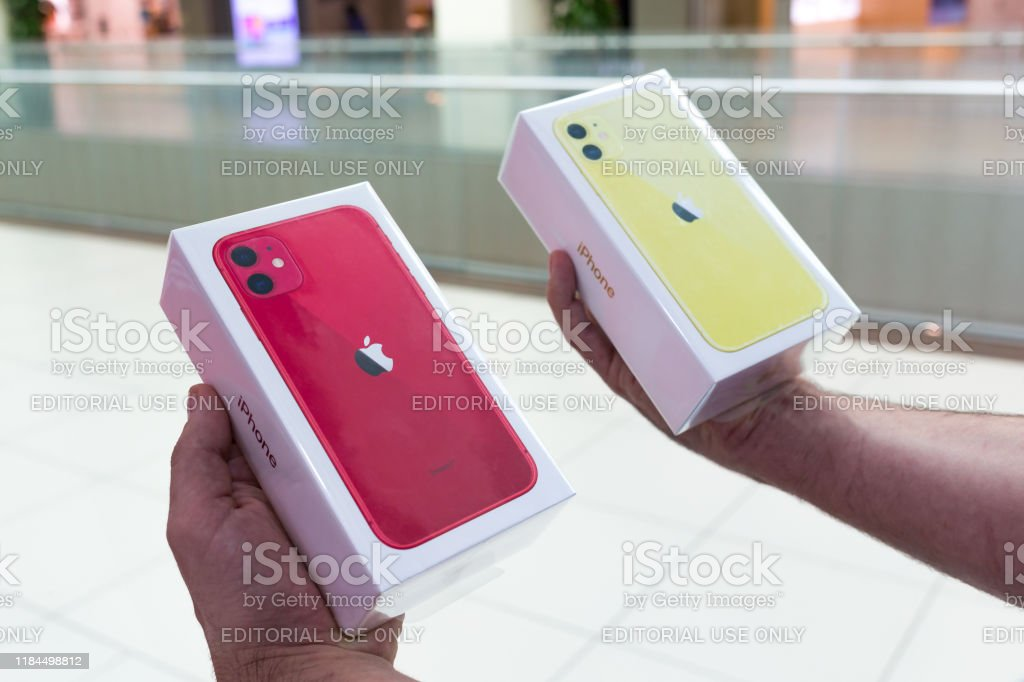 Apple iPhone 11 and 11 Pro mobile smartphones in hands Belgrade, Serbia - October 25, 2019: New Apple iPhone 11 is displayed in original packages in hands. Two cardboard boxes close-up. Advertisement Stock Photo