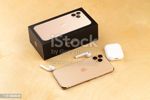 istock Apple iPhone 11 Pro on a wooden surface. Apple's new smartphone close-up. Smartphone and AirPods earphones and a box from it. 1181690649