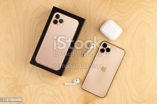istock Apple iPhone 11 Pro on a wooden surface. Apple's new smartphone close-up. Smartphone and AirPods earphones and a box from it. 1181690699