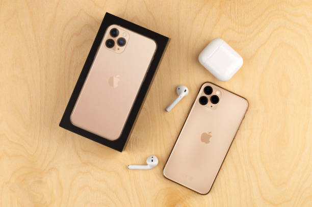 apple iphone 11 pro on a wooden surface. apple's new smartphone close-up. smartphone and airpods earphones and a box from it. - iphone zdjęcia i obrazy z banku zdjęć