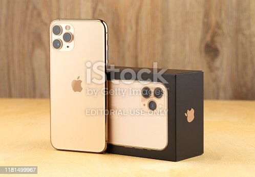 istock Apple iPhone 11 Pro on a wooden surface.  New smartphone from the company Apple close-up. Smartphone and box from it. 1181499967