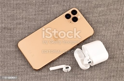 istock Apple iPhone 11 Pro on gray knitted fabric. New smartphone from the company Apple close-up. Smartphone and AirPods earphones. 1181689641