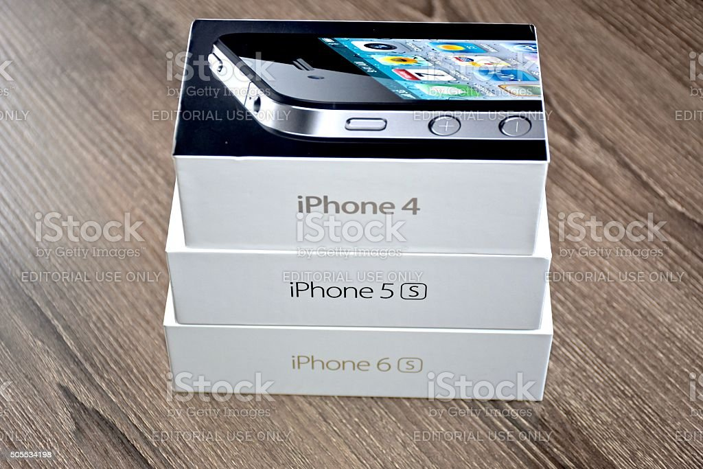 Apple iPhone 4, 5s, and 6s on a wood surface stock photo