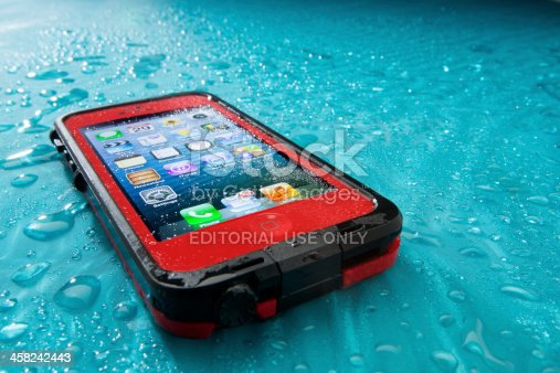 San Diego, California, United States - July 29th, 2013: This is the Apple iphone 5 in a red lifeproof case. It was photographed in the studio at a low angle and spritzed with water. Apple Inc. is the leading manufacturer in smart phones. It recently released the new IOS 7 operating system. Lifeproof caes enable the iPhone to be submersed up to 6 1/2 feet of water and protect it from falls and dirt as well.