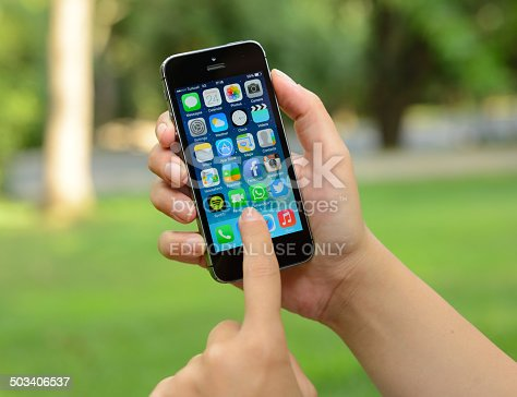 İstanbul, Turkey - July 24, 2014: Woman hands holding and touching an Apple iPhone 5 s in a park. iPhone 5 s is a smart phone produced by Apple Computer, Inc
