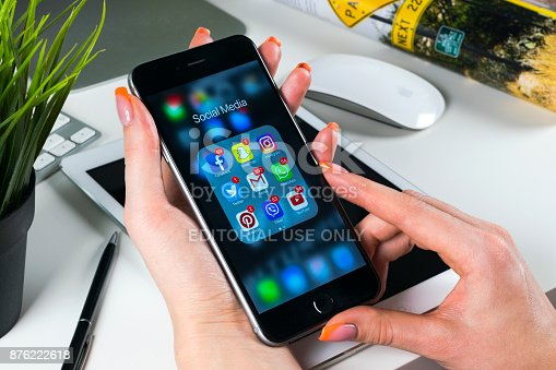 istock Apple iPhone 7 in woman hand with icons of social media facebook, instagram, twitter, snapchat application on screen. Tablet computer life style. Starting social media app. 876222618