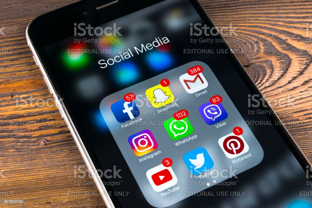 Apple iPhone 7 auf Holztisch mit Icons von social-Media Facebook, Instagram, Twitter, Snapchat Anwendung auf dem Bildschirm. Tablet-Computer Life-Style. Social-Media-app starten. – Foto