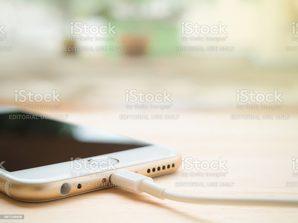 Apple iPhone charging battery on wooden table stock photo