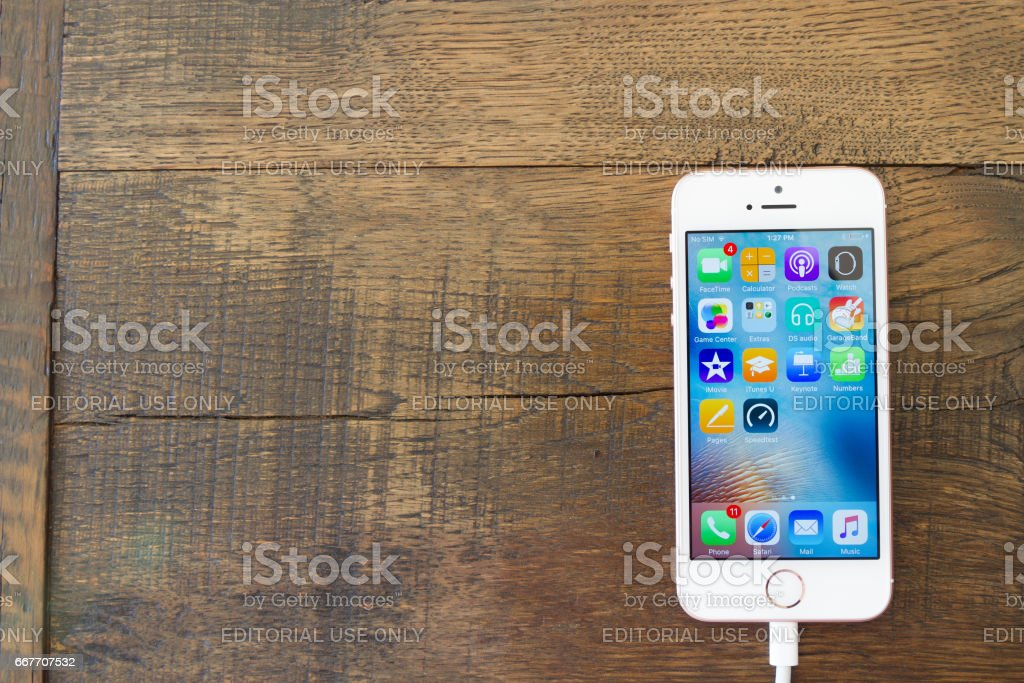 Apple iPhone SE smartphone on wooden back ground. It was unveiled on March 21, 2016,  was released on March 31, 2016. stock photo