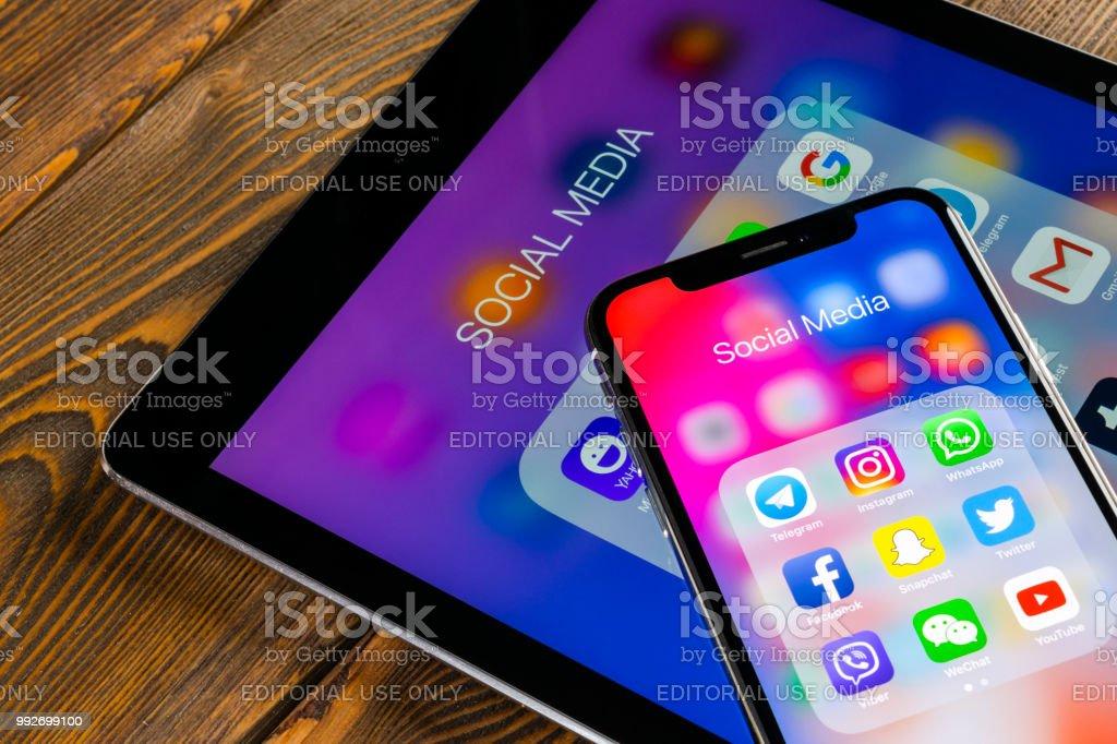 Apple iPhone X und iPad am Schreibtisch mit Icons von social-Media Facebook, Instagram, Twitter, Snapchat Anwendung auf dem Bildschirm. Soziales Netzwerk. Social-Media-app starten. – Foto