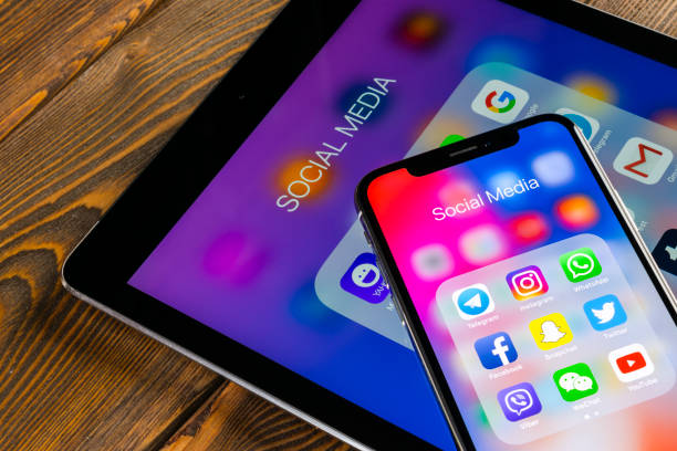 Apple iPhone X and iPad on office desk with icons of social media facebook, instagram, twitter, snapchat application on screen. Social network. Starting social media app. stock photo