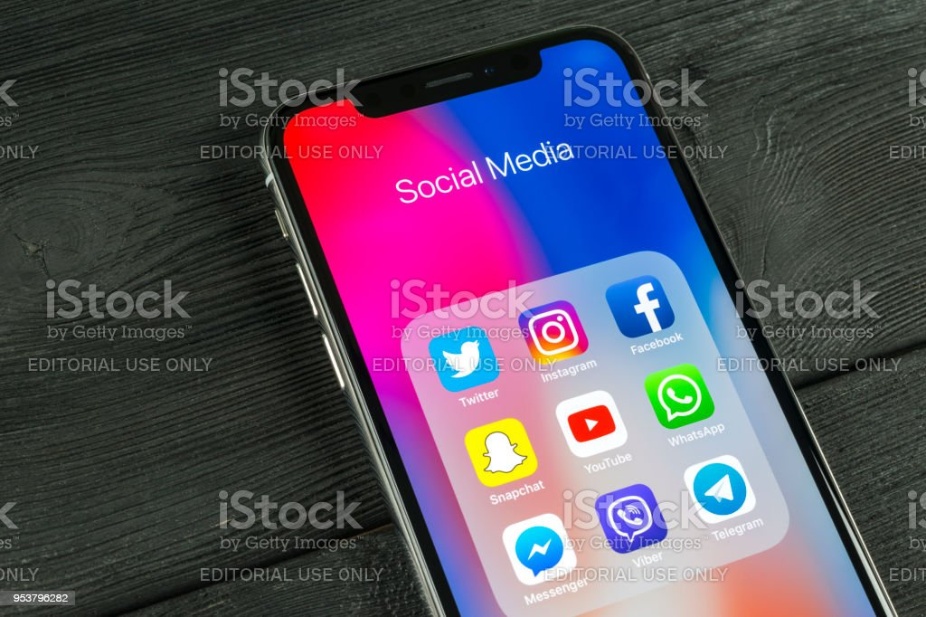 Apple iPhone X am Schreibtisch mit Icons von social-Media Facebook, Instagram, Twitter, Snapchat Anwendung auf dem Bildschirm. Soziales Netzwerk. Social-Media-app starten. – Foto