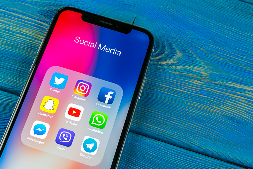 istock Apple iPhone X on office desk with icons of social media facebook, instagram, twitter, snapchat application on screen. Social network. Starting social media app. 962440944