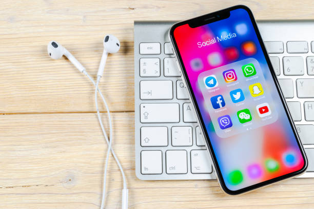 apple iphone x on office desk with icons of social media facebook, instagram, twitter, snapchat application on screen. social network. starting social media app. - instagram стоковые фото и изображения