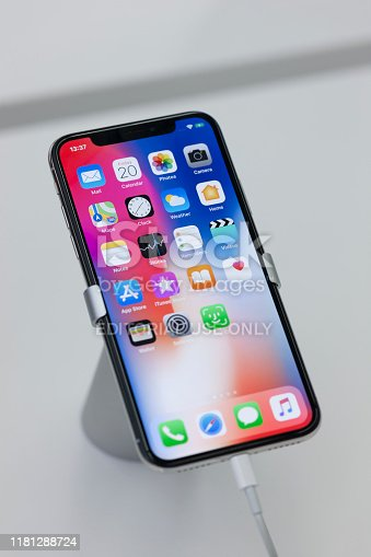 New York, USA - July 20, 2018: Apple iPhone X Silver smartphone  on display stand in a technology store. Apple iPhone X is  with 5.8 inch display, face detection and made entirely of glass.The front is only a display without fingerprint button.Unlocking of the phone is possible only with the detection of the owner's face.