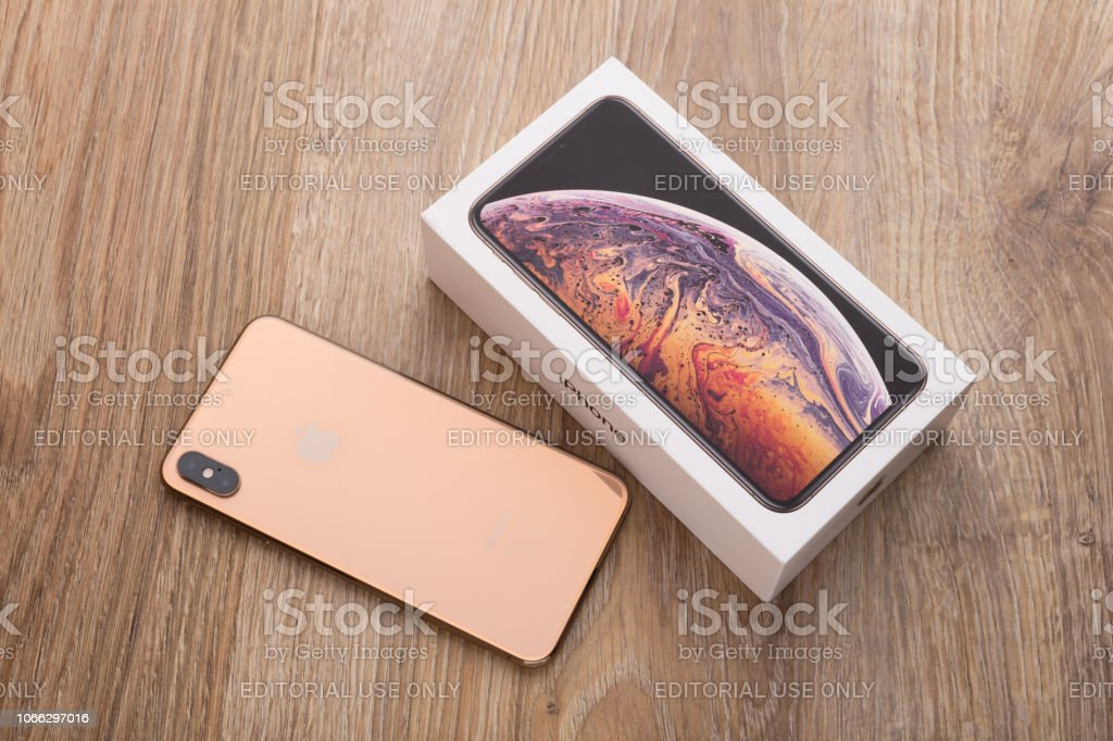 Apple iPhone XS Max 6.5-inch display and box on a wooden surface.