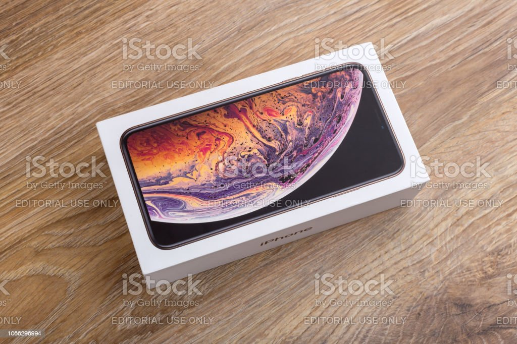 Apple iPhone XS Max 6.5-inch display in a box on a wooden surface.