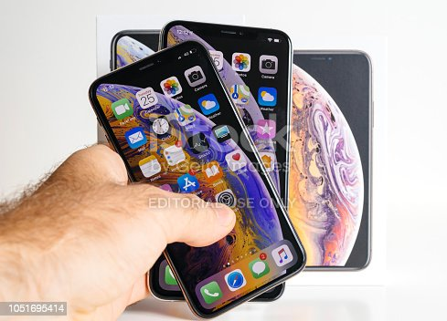 istock Apple iPhone Xs Max Gold Silver Smartphone in man's hand 1051695414