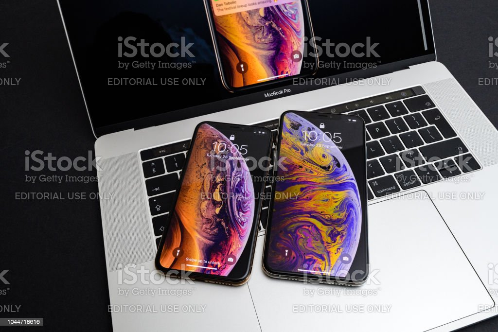 Apple iPhone Xs Max Gold Silver Smartphone on laptop stock photo