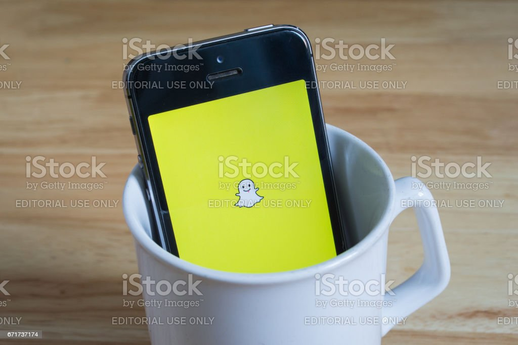 Apple iPhone5s in a mug showing its screen with Snapchat logo. - Foto stock royalty-free di Applicazione mobile