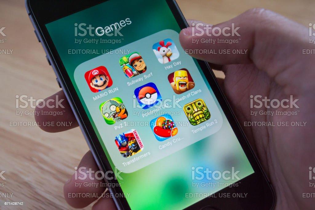 Apple iPhone5s mostra a sua tela com Pokemon Go, Mario Run e outros aplicativos de jogos populares. - foto de acervo