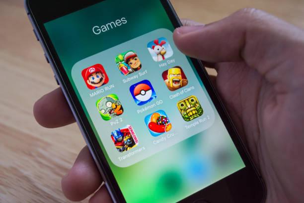 apple iphone5s zeigt seinen bildschirm mit pokemon gehen, mario run und andere beliebte spielanwendungen. - plants of zombies stock-fotos und bilder