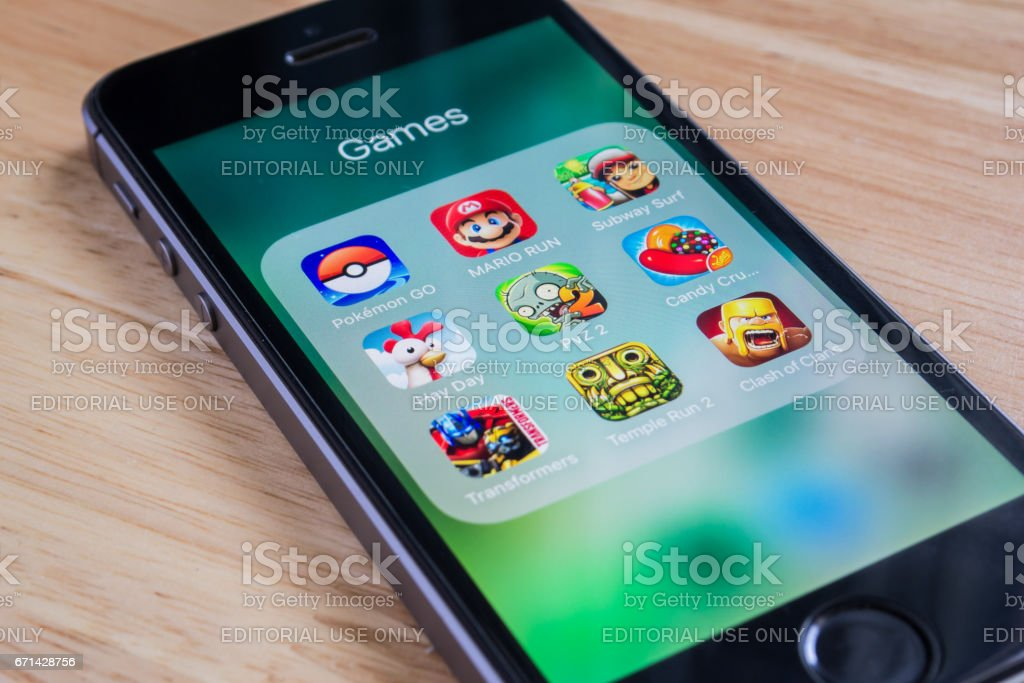 Apple iPhone5s showing its screen with Pokemon Go, Mario Run and other popular game applications. stock photo