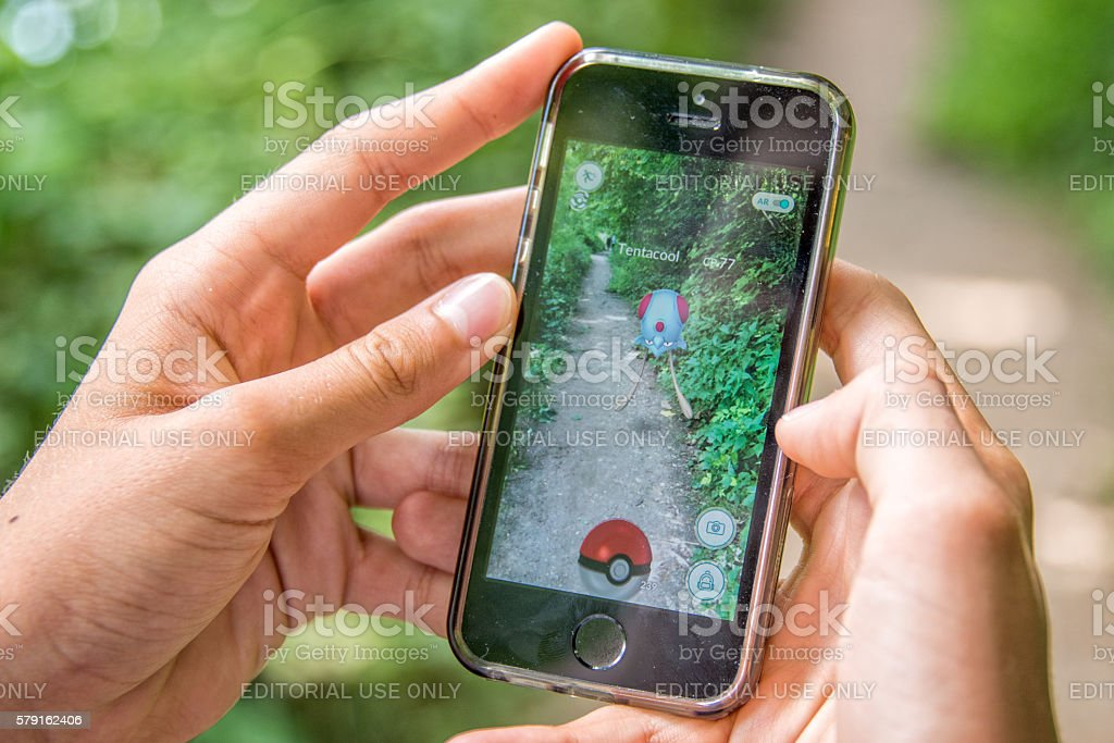 Apple iPhone5s with Pokemon Go application, hands of a teenager stock photo