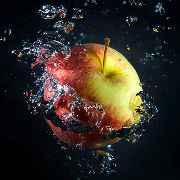Apple is under water in a stream of air bubbles stock photo