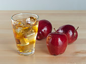 A Glass of Fresh Cold Apple Juice with Ice Beside Apples on A Wooden Table Background