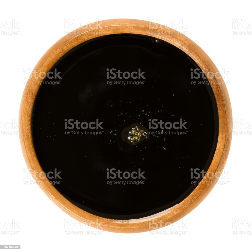 Apple juice concentrate in wooden bowl over white stock photo
