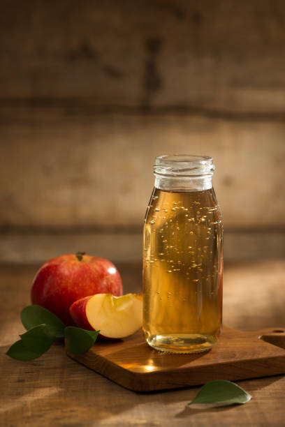 Apple juice in a bottle and glass with sliced red apple in wooden background stock photo