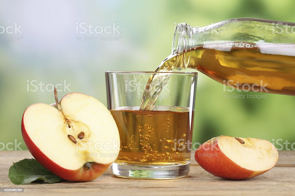 Apple juice pouring from red apples into a glass stock photo