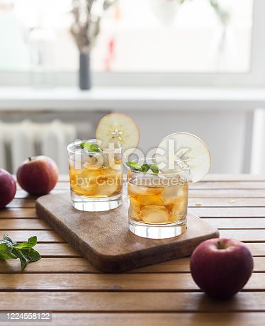 Apple juice with ice and garnish on wooden background. Concept of freshness lemonade beverage at sunny day