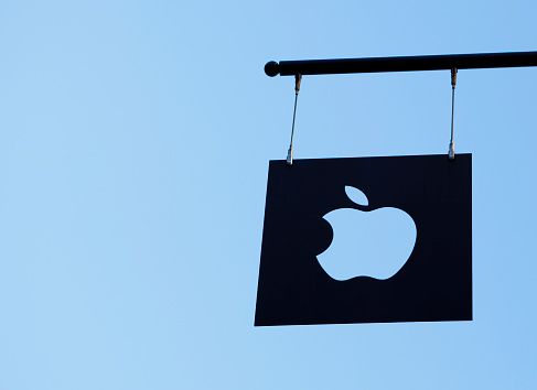 New York, New York, USA - March 27, 2011: An Apple Logo cutout plate flag hangs against a blue sky from the Apple Store in Soho New York City.