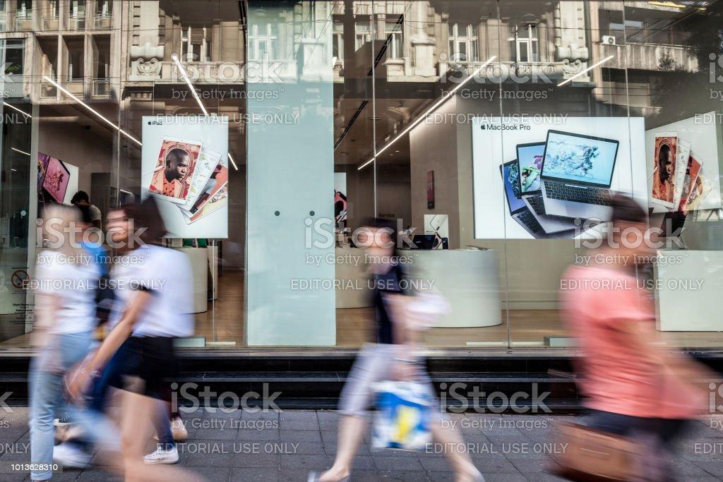 Logotipo da Apple na Apple Store de Belgrado premium revendedor twith as pessoas passando na frente. Apple Store é uma cadeia de lojas de varejo, pertence e é operado pela Apple Inc. - foto de acervo
